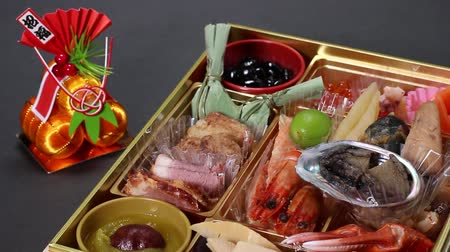 crab eating : Japanese New Year dishes Osechi-Ryori and ornament.letters meaning Congratulations and Invitations Stock Footage