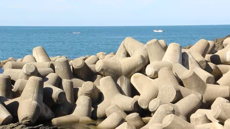 borracha : Tetrapod breakwaters in sea water and fishing boats Stock Footage