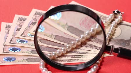 expansion : 10000 yen bill, pearl necklace and magnifying glass