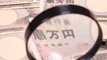 magnifier : 10000 Yen bills and magnifying glass.