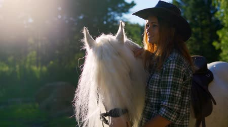 Çingene : The girl looks dreamily into the distance. Portrait of a young girl in a cowboy hat near a horse, close-up. Slow motion. Sunset light.