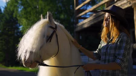 Çingene : A young girl in a cowboy hat takes care of and caresses a horse on an animal farm on a hot summer day. Slow motion