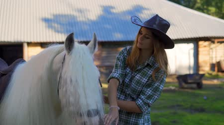 kısrak : A young girl in a cowboy hat takes care of and caresses a horse on an animal farm on a hot summer day. Slow motion