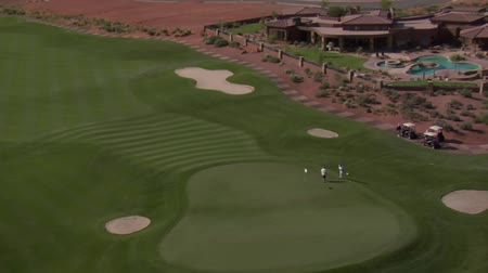 deserto : Aerial shot of golfers on the desert course zoom out