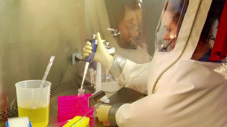 naukowiec : scientist in bubble suit uses pipette to transfer samples Wideo