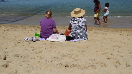 piknik : two ladies sit on sandy beach