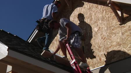 zastřešení : men climb down ladder on house construction