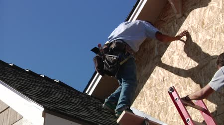 zastřešení : man with toolbelt climbs down roof