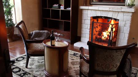 cozy : cozy chairs in front of fireplace with bottle of wine