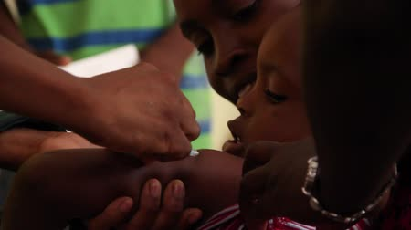 homeless : child receives vaccine shot in Haiti Stock Footage