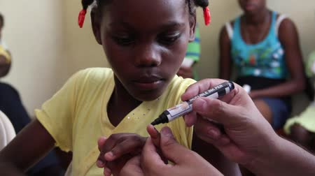 homeless : Child receives fingernail mark in Haiti Stock Footage
