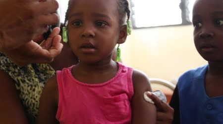 homeless : child receives fingernail mark after vaccination in Haiti