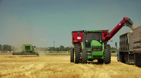 traktor : tractor loads we into semitruck combine in distance