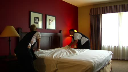 отель : housekeepers in the hotel room change bedding