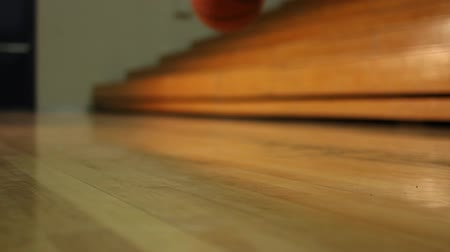 atletismo : Basketball bouncing on gym floor near bleachers Stock Footage