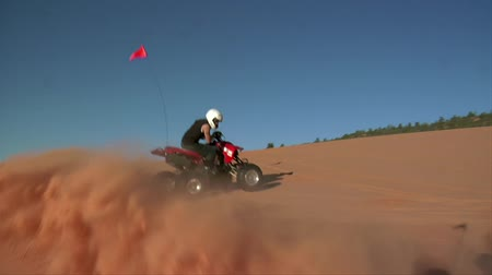 slow-motion ATV riders on sand dunes