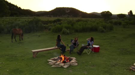 şenlik ateşi : three women sit around a campfire Stok Video