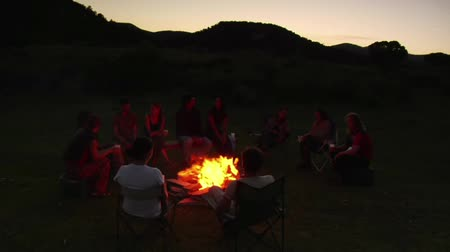 kamp ateşi : group sits around campfire at dusk Stok Video