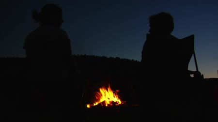 şenlik ateşi : silhouettes of two people around campfire
