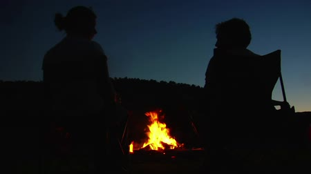 костер : silhouettes of two people around campfire