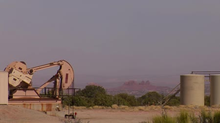 mudança : oil pump in red rock desert with tanks Stock Footage