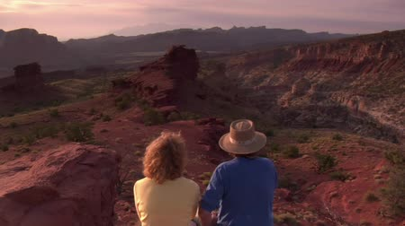 casado : couple sits on a red rock cliff and admires view Capitol reef national Park