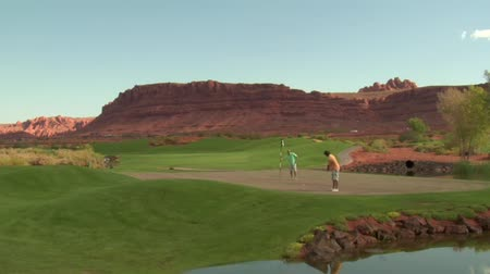 companionship : father and son putt on golf course with pond and red rock cliffs Stock Footage