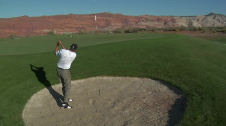 ловушка : jib  shot of man hitting a golf ball from sand trap