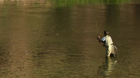 ловушка : young man flyfishing with fish on line