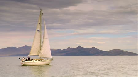 sima : A sailboat glides on calm water near mountains