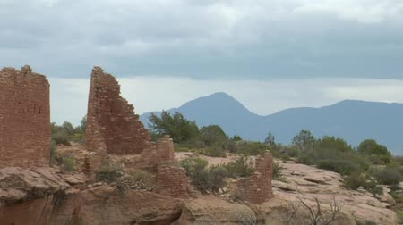 руины : zoom out shot of mountains revealing ruins  at Hovenweep national Monument