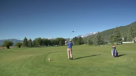 поле для гольфа : jib shot of man teeing off on golf course with snowy mountains indistance Стоковые видеозаписи
