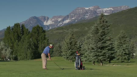 тройник : zoomed shot of man teeing off on golf course with snowy mountains indistance Стоковые видеозаписи