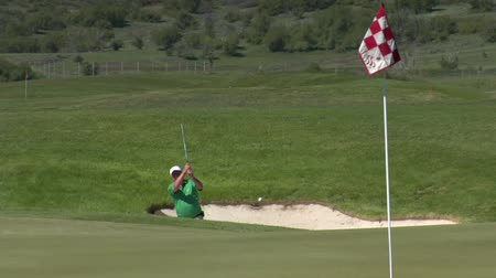 ловушка : slow-motion shot as  Man chips out of sand trap  to green with snowy mountains in distance Стоковые видеозаписи