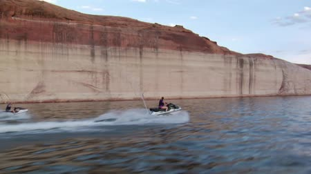 couple riding jet skis on Lake with a red rock cliffs