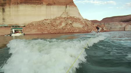 vodní sporty : young man gets up wake boarding behind ski boat Lake Powell Utah