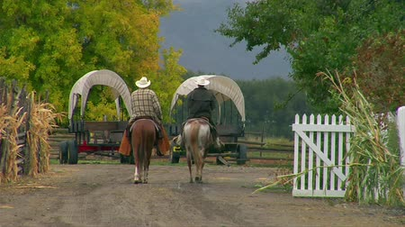 konie : two men on horses walk by covered wagons