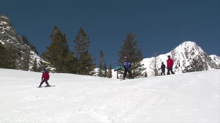 zahmetsiz : Family of skiiers glide down hill, blue sky day