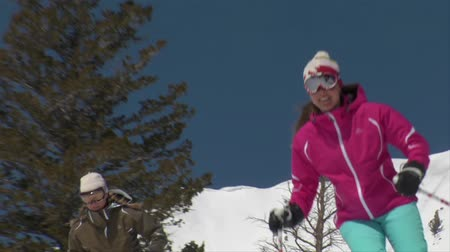 bezmotorové létání : Female skiers glide past camera on blue-sky day