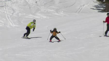 ailelerin : Little skier snow-plows intently , parents follow Stok Video