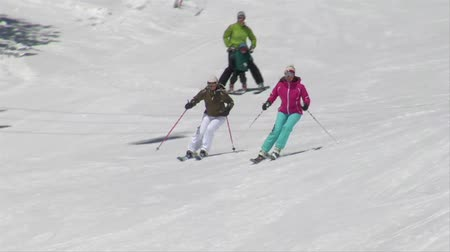 bezmotorové létání : A group of skiers glide down hill on blue-sky day Dostupné videozáznamy