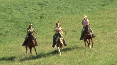 koń : three young women on horses gallop across green meadow- tight shot