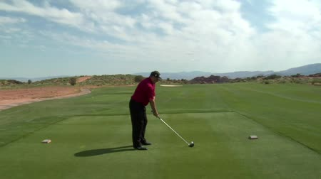 golfjátékos : steadicam shot as man tees on golf course with red rock cliffs and distance Stock mozgókép