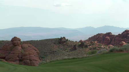golf sahası : light changes on red rock cliffs with green golf course in foreground