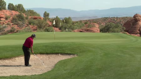golfjátékos : slow-motion shot of golfer chipping out of sand trap onto green