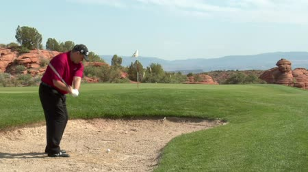 golf sahası : shot of golfer chipping out of sand trap onto green
