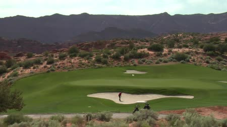 golf sahası : wide shot of golfer hitting ball from sand trap to green