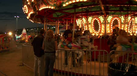 targi : parents watch their kids on carousel Wideo