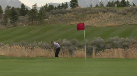 upadek : golfer chips onto green with red flag and snowing mountains