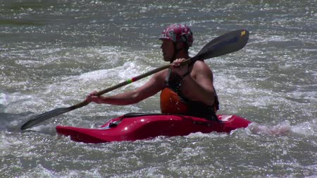 man paddles in Rapids using white-water kayak
